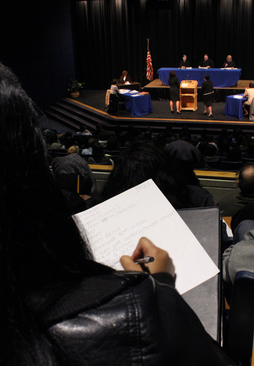 Photo of a paralegal student taking notes in court.