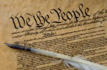 Photo of the Constitution of the United States of America and a feather quill