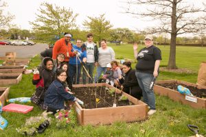 SSC students work in a garden for pollinators plant young plants with SSC Green's Alysia Robinette, the event's coordinator