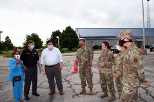 Dr. Lynette D. Stokes, South Suburban College President; JB Pritzker; Illinois Governor; Frank M. Zuccarelli, Chairman of the SSC Board of Trustees; and members of the National Guard discuss the opening of the new COVID-19 testing facility